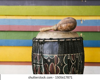 Percussion instruments alongside multicolored stripes wall with copy-space
