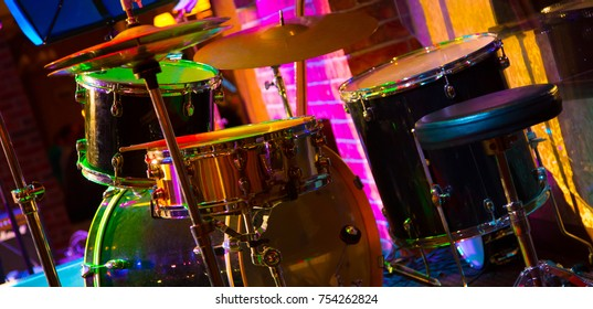 Percussion Musical instruments. Beautifu music background. Drum set on the stage in multicolored rays of concert light closeup with selective focus. Colorful Wide Screen Wallpaper or Web Banner