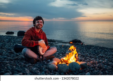 percussionist guy plays a djembe sitting on the beach by the fire at sunset.