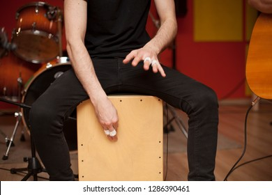 Percussionist playing cajon on a rehearsal studio with drums and music stuff on the background