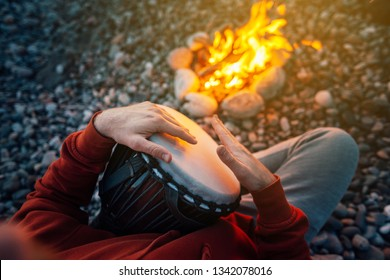 percussionist playing djembe sitting by the fire, close-up