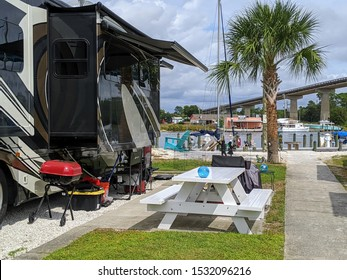 PERDIDO KEY, FLORIDA - OCTOBER 15, 2019:  A luxury rv motorhome's camp site is set up for glamping under palm tree along the waters in Florida