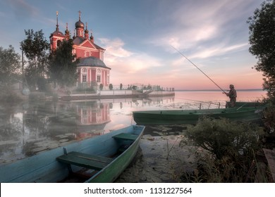 Pereslavl-Zalessky, Russia. 07 JULY 2018: Fisherman early in the morning is fishing near the river. The Church of the Forty Martyrs of Sebaste in Pereslavl-Zalessky, Russia.