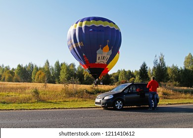 Pereslavl-Zalessky, Russia - September 23, 2017: Man near the car watching as two hot air balloons land on the field at the festival of aeronautics in Pereslavl-Zalessky