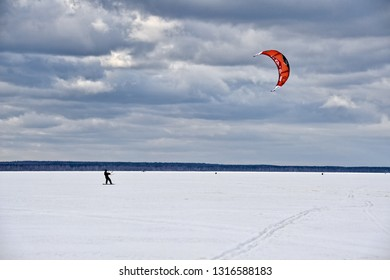 PERESLAVL-ZALESSKY, YAROSLAVL REGION, RUSSIA - February 17, 2019 Snow Kiting on Pleshcheyevo Lake. Snowboarder with red kite rides on a frozen Pleshcheyevo Lake in Pereslavl-Zalessky under grey skies.
