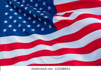 Perfect American flag waving on a sunny day Stars and Stripes representing Independence Day memorial symbol for the United States of America close up on Stars and Stripes