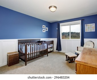 Perfect baby room with beautiful deep blue walls, and stained wood crib.
