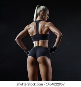 Perfect back muscles of a female athlete buttocks on black background. Female bodybuilder turned back wearing gloves ready for gym exercise. Fitness exercising. Energy fitness motivation.