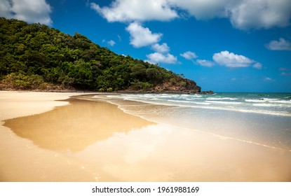Perfect beach, Daintree beach in Queensland, Australia. Clean, wide sand beach with turquoise water, blue sky with white clouds. Headland covered with thick rainforest.