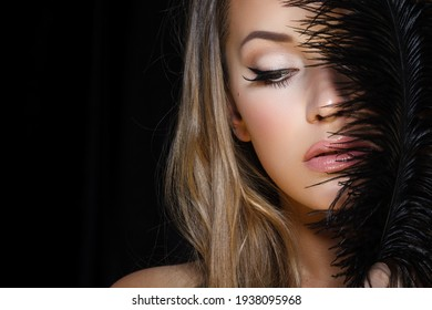 Perfect beauty and glamour concept. Portrait of beautiful female model holding black feather on dark background. Young blond woman shows glamorous finery.