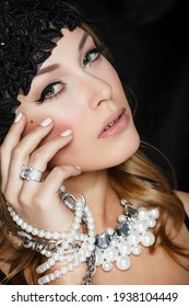 Perfect beauty and jewelry concept. Portrait of beautiful female model wearing ring, necklace and wristband on black background. Young blond woman shows glamorous finery.