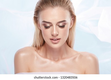 Perfect blonde girl at white background wearing dress and nude make up, portrait. Girl with wet hair and blue eyes, naked shoulders, looking down.