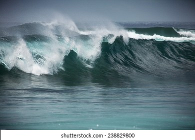 perfect blue wave in the sea water and grey sky