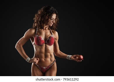 Perfect body Fitness woman bodybuilder in red bikini hold red apple isolated posing over black background in studio. Beautiful sporty girl fitness bikini model.