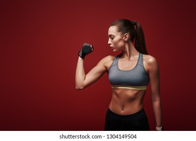 Perfect body. Sportswoman is training with dumbbells standing over red background