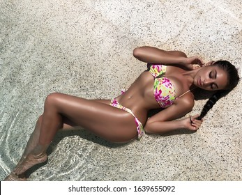 Perfect body woman bikini model at sand tropical beach. Young girl in bright swimsuit summer outdoors portrait. Glamour fashion lady relaxing near ocean water. Tanned fitness body woman