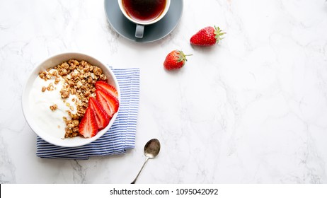 Perfect breakfast: crunchy granola with yoghurt and strawberries with a cup of black coffee on marble table. Flat lay with copy space