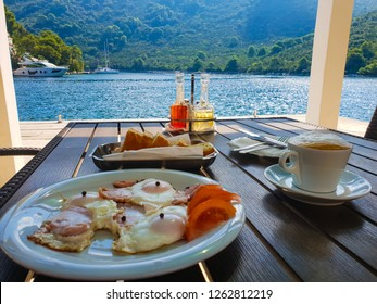 The perfect breakfast: freshly fried eggs with ham and tomatoes and a cup of cappuccino outdoord on the terrace of the restaurant at the sea, sunny summer day, Mljet island, Croatia, Adriatic sea