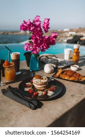 The perfect breakfast in Mykonos. Iced Coffee, orange juice, pancakes, chocolate croissant, fruits and greek yogurt; The pleasure to eat this breakfast in front of the aegan sea