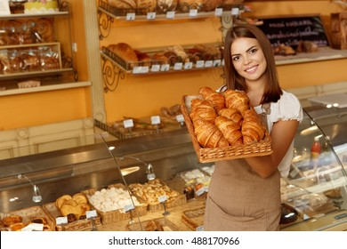 Perfect for breakfast. Shot of a gorgeous young woman holding a basket full of freshly baked croissants she is selling at her bakery copyspace