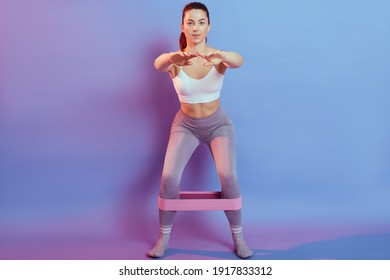Perfect buttocks. Front view of young and slim European woman in sports clothing doing squat exercises with resistance band while standing against color background, keeps hands in front of chest.