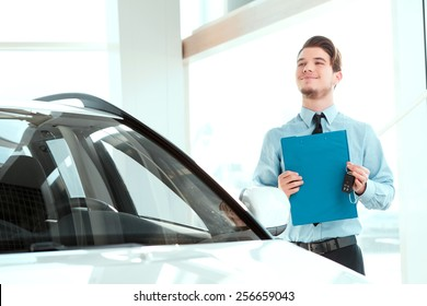 Perfect car dealer. Portrait of handsome young car sales man in formalwear holding a clipboard and looking up while standing by a new suv in a car dealership