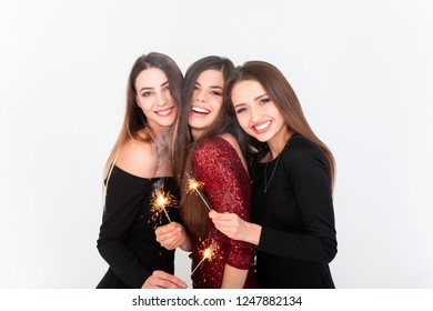 Perfect celebration night concept. Beautiful young women looking at camera and holding sparkler with smile while standing against white background