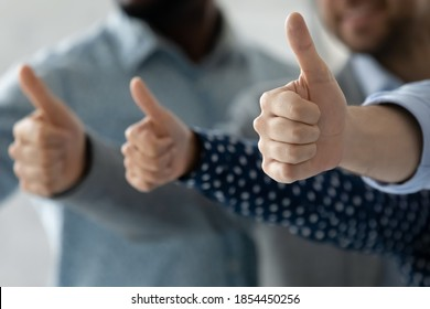Perfect choice for everyone. Close up of multiethnic men and women hands raised in thumbs up gesture approving recommending best contract or loan terms conditions, qualified goods service assistance
