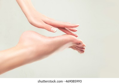 Perfect clean female feet . Beautiful and elegant groomed girl's hand touches her feet . Spa ,scrub and foot care .