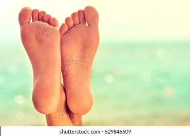 Perfect clean female feet  with sea sand on the beach .   . Spa ,scrub and foot care . Foot massage .