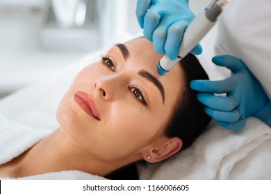 Perfect cleansing. Face of a beautiful pleasant woman being cleansed during hydrafacial procedure