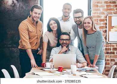 Perfect creative team. Group of six cheerful young people looking at camera with smile while leaning to the table in office