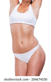 Perfect curves. Close-up of beautiful young woman in white bra and panties keeping arms raised while posing against white background