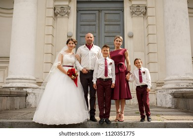 Perfect daughter bride with parents and younger brother posing at camera while taking a picture at the wedding day. Standing near the ancient building.