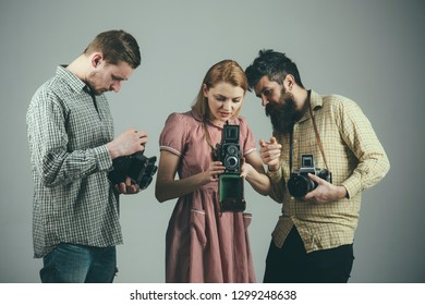The perfect day to make good shots. Group of photographers with retro cameras. Paparazzi or photojournalists with vintage old cameras. Retro style woman and men hold analog cameras. Photo studio.