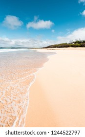 Perfect Day in Molokai Hawaii with Beautiful Island Paradise of Clear Aqua Blue Ocean Waves Coming on Sandy Golden Seashore and White Sand Beach and Rock Cliffs