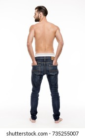 Perfect denim. Rear view full length of young shirtless man in jeans looking away while standing against white background.