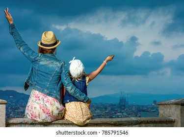 Perfect evening with stunning view. Seen from behind trendy mother and child travellers against cityscape of Barcelona, Spain rejoicing