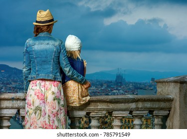 Perfect evening with stunning view. Seen from behind elegant mother and daughter travellers against city panorama of Barcelona, Spain looking into the distance