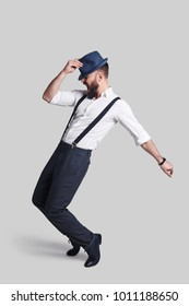 Perfect in every way. Full length of handsome young man in suspenders adjusting his hat and making a face while dancing against grey background