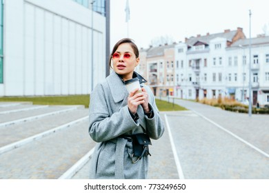 The perfect fall outfit. fashion female blogger on the street in pink glasses, gray oversized coat, small black waist bag drinking coffee to go. Lifestyle and cold weather concept.