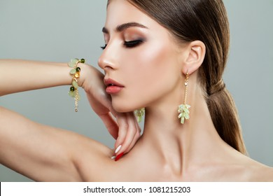 Perfect Fashion Model Woman with Gold Jewelry. Attractive Lady with Bracelet and Earrings