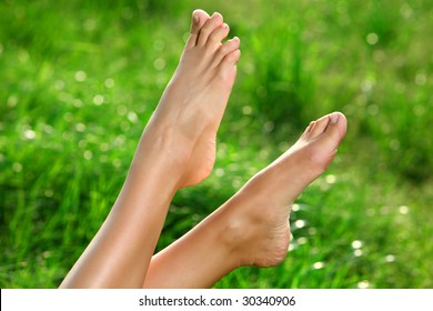Perfect Feet in the sun with shaved legs on a meadow of a young sexy woman or girl