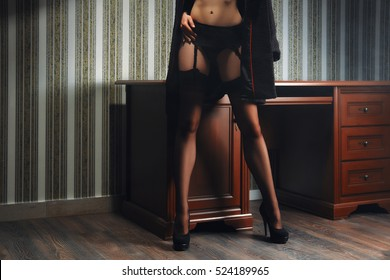Perfect female legs in black stockings with suspender belt. Slim lady near the table.