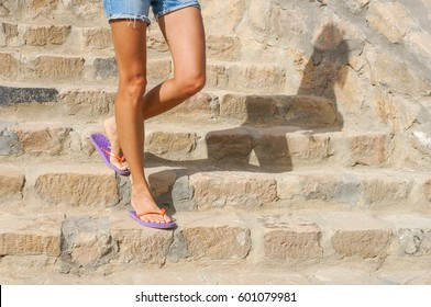 Perfect female legs in summer sandals walking on a resort city