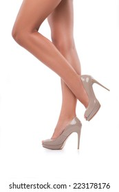 Perfect female legs wearing grey high heels isolated on white background