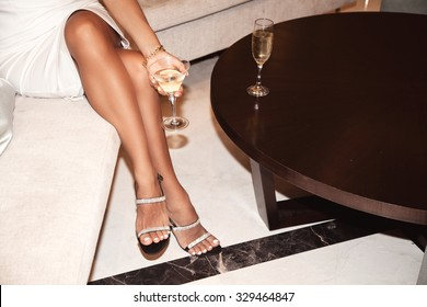 Perfect female legs wearing high heels. Woman drinking champagne. Holidays and relaxation concept
