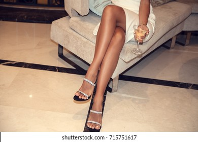 Perfect female legs wearing high heels. Woman drinking champagne. Holidays and celebration concept