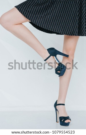 09abf0fed Perfect female legs wearing high heels isolated on white background.Woman  long legs in fashion dress