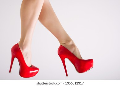 Perfect female legs wearing red high heels isolated on white background